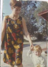 """Helen Rayner, USA, 1963 - My mother moved with me (the toddler in the photo) from the UK to California in 1963. She can't remember the dress, but I feel I know it - just from seeing it in this photograph over the years. She has her hair back-combed and swept up into a bun here, but soon after this photograph was taken, she started to wear her hair long and straight - often with a flower in it. One day in San Francisco a visitor to the city called out on seeing her, """"Look, they DO wear flowers in their hair!"""""""