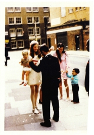 My mother (in white! Why would she?) at my aunt's wedding in London 1969 holding me (wearing a spiffing pair of red shoes). Despite the absolute no-no of wearing white to someone else's wedding she does look very elegant and typically 60's.