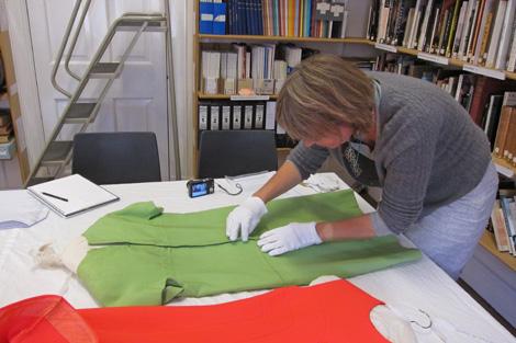 Anna Glasbrook, with cotton gloves, examining BATMC I.09.884, Nina Ricci, 1967 silk plain weave dress (also has a separate coat).