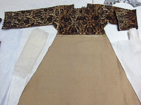 A decorated linen smock, hand embroidered with silk in England, 1575 - 1585.  The skirt and lace trim are modern.